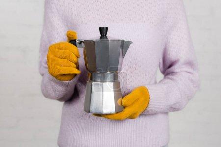 Ausgeschnittene Ansicht einer Frau in Handschuhen und warmem Pullover mit Geysir-Kaffeemaschine auf weißem Hintergrund