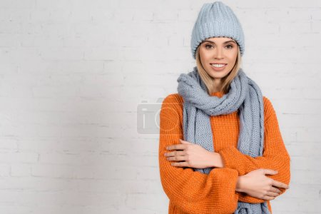 Stylish woman in cozy sweater, hat and scarf smiling at camera on white background