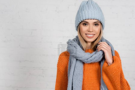 Cheerful woman in scarf and warm sweater near white brick wall