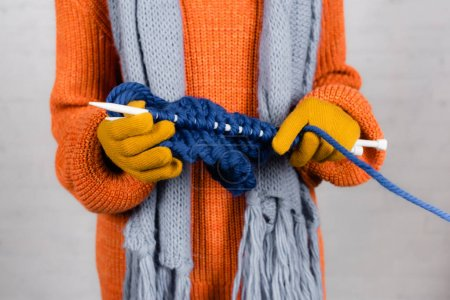 Photo for Cropped view of woman in gloves and sweater knitting on white background - Royalty Free Image