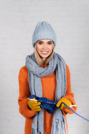 Smiling woman in warm clothes knitting on white background