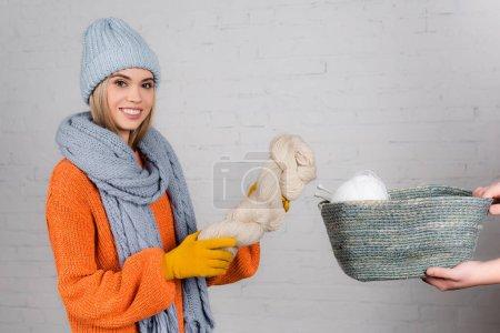 Photo pour Femme souriante en vêtements chauds tenant fil près de l'homme avec panier sur fond blanc - image libre de droit