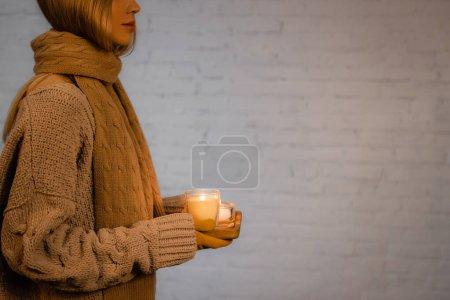 Foto de Vista recortada de la mujer en suéter, bufanda y guantes que sostienen velas ardientes cerca de la pared de ladrillo blanco - Imagen libre de derechos