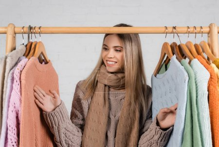 Photo for Cheerful woman in scarf looking at sweaters on hanger rack on white background - Royalty Free Image
