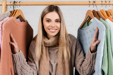 Woman in scarf smiling at camera near warm sweaters on hanger rack on white background