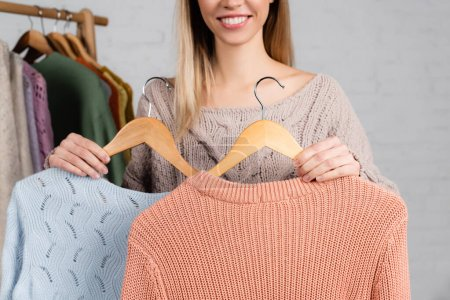 Photo for Cropped view of hangers with sweaters in hands of smiling woman blurred on white background - Royalty Free Image
