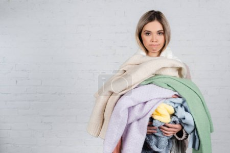 Skeptical woman holding knitwear and looking at camera on white background