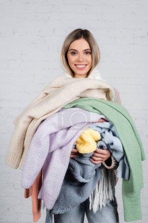 Mujer sonriente sosteniendo suéteres de punto y mirando a la cámara sobre fondo blanco