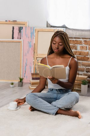 African american woman reading book and holding cup of coffee on carpet at home