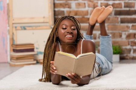 Smiling african american woman reading book while lying on carpet at home