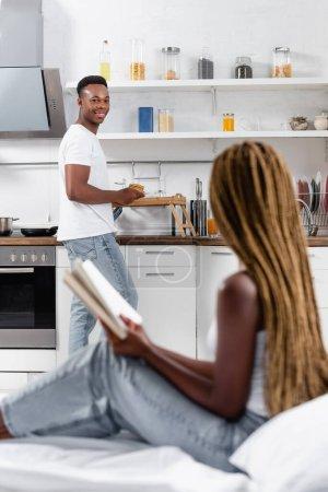 Lächelnder afrikanisch-amerikanischer Mann hält Pfannkuchen neben Tablett und Freundin mit Buch auf verschwommenem Vordergrund auf dem Bett