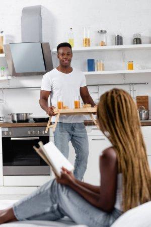 Photo pour Homme africain souriant tenant plateau avec petit déjeuner savoureux près de la petite amie avec livre sur le lit au premier plan flou - image libre de droit