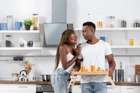 Photo for Smiling african american woman hugging boyfriend with delicious breakfast and orange juice on tray in kitchen - Royalty Free Image