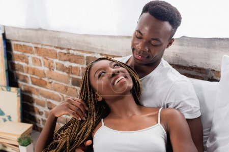 Photo for Positive african american woman looking at boyfriend at home - Royalty Free Image