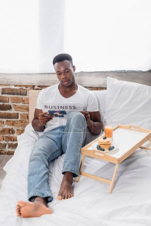 Photo for African american man reading business newspaper near pancakes and orange juice on bed - Royalty Free Image
