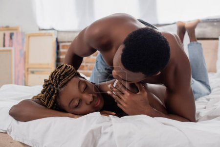 Shirtless african american man touching girlfriend on bed