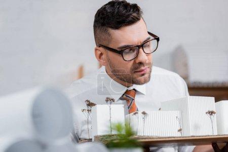 Photo pour Architecte sérieux dans les lunettes regardant les modèles de bâtiments dans le bureau, au premier plan flou - image libre de droit