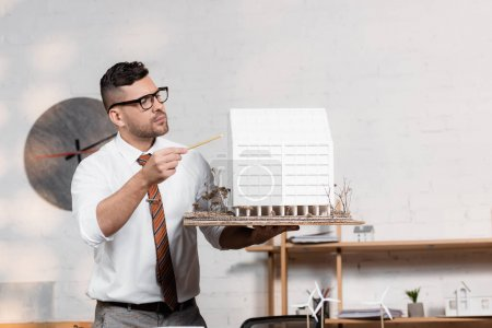 Foto de Arquitecto serio en anteojos apuntando con lápiz a modelo de casa - Imagen libre de derechos