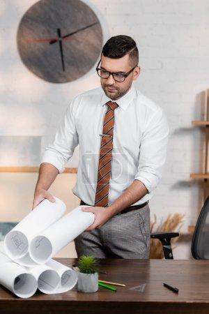 Foto de Arquitecto en anteojos sosteniendo plano mientras está parado en el lugar de trabajo - Imagen libre de derechos
