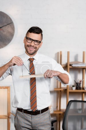 Photo for Positive architect looking at camera while holding ruler and divider in office - Royalty Free Image