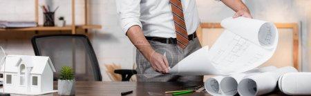 Photo pour Vue partielle du plan de maintien de l'architecte près du modèle de la maison et des plans roulés sur le bureau, bannière - image libre de droit