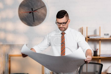 Photo for Thoughtful architect in eyeglasses holding blueprint in office - Royalty Free Image