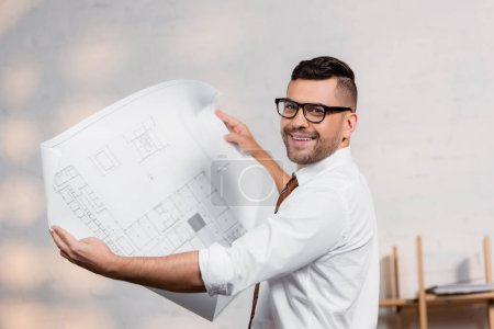 happy architect in eyeglasses looking at camera while holding blueprint