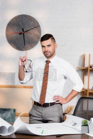 Photo pour Architecte souriant pointant vers le haut avec le doigt tout en se tenant avec la main de la hanche près des plans - image libre de droit