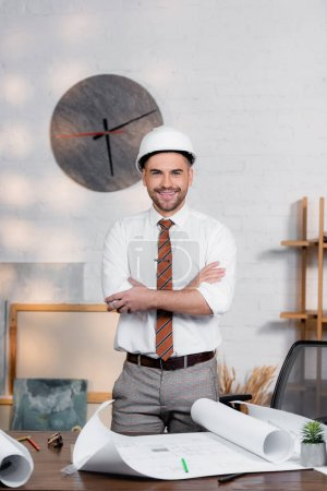 happy architect in helmet standing with crossed arms near blueprints on desk