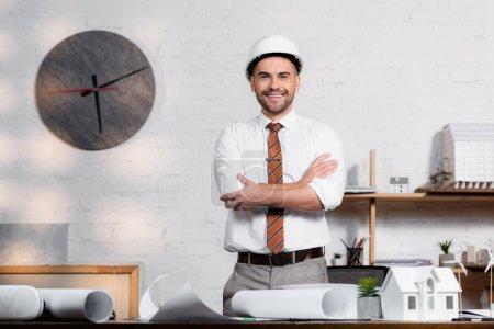 Foto de Arquitecto sonriente en casco de pie con brazos cruzados cerca de planos y modelo de casa - Imagen libre de derechos