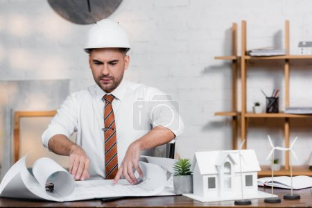 Foto de Arquitecto serio en casco mirando plano cerca de modelo de casa - Imagen libre de derechos