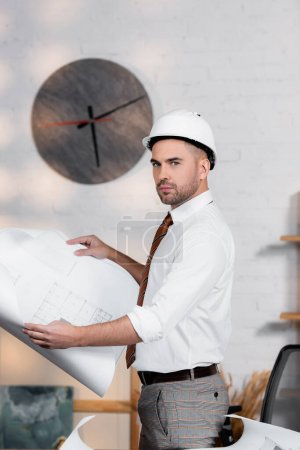 Photo for Serious architect in helmet holding blueprint and looking at camera - Royalty Free Image