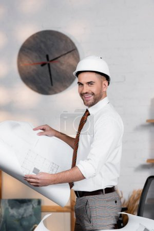 Photo for Happy architect in helmet looking at camera while holding blueprint - Royalty Free Image