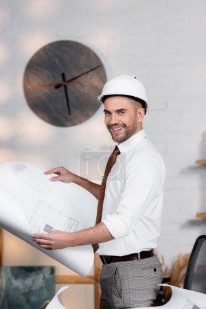 Foto de Arquitecto feliz en casco mirando a la cámara mientras sostiene el plano - Imagen libre de derechos