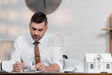 concentrated architect working with pencil and divider on blueprint near house model