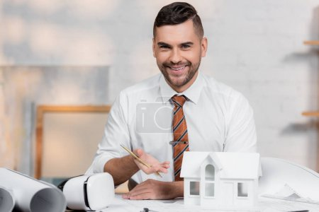 happy architect looking at camera while pointing at house model