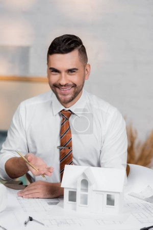 smiling architect looking at camera while pointing at house model