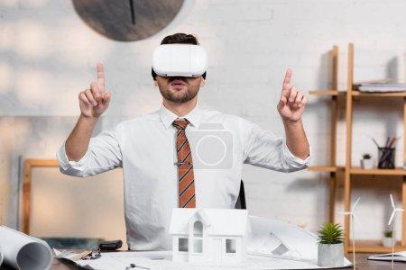 Architekt im vr-Headset zeigt mit den Fingern, während er am Arbeitsplatz in der Nähe des Hausmodells sitzt
