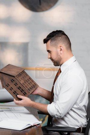 Foto de Vista lateral del arquitecto sosteniendo el modelo de la casa mientras está sentado en el lugar de trabajo - Imagen libre de derechos
