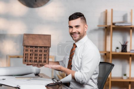happy architect smiling at camera while pointing at house model at workplace