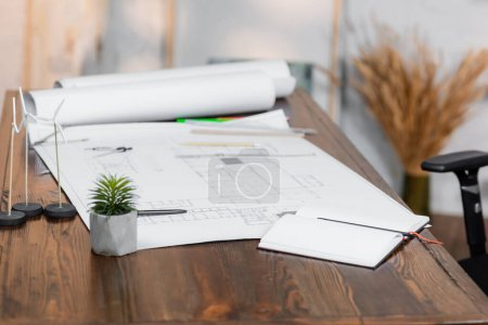 Photo for Empty notebook, blueprints and wind generators models on desk in office, blurred background - Royalty Free Image