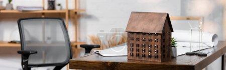 Photo pour Maquette de maison près des éoliennes maquettes sur bureau en bureau d'architecture, bannière - image libre de droit