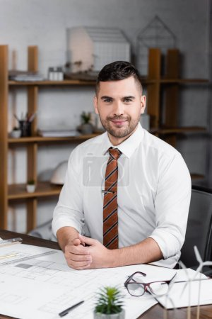Photo for Happy architect looking at camera while sitting at workplace near blueprint, blurred foreground - Royalty Free Image
