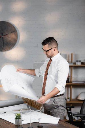 architect holding blueprint near models of wind turbines on desk