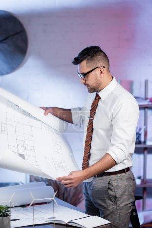 Photo pour Architecte sérieux à la recherche d'un plan près des modèles d'éoliennes sur le bureau - image libre de droit