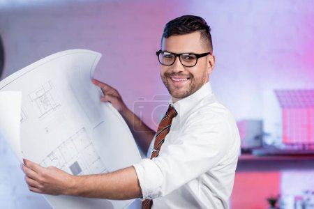 happy architect in eyeglasses smiling at camera while holding blueprint