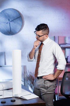 Nachdenklicher Architekt steht mit der Hand auf der Hüfte am Arbeitsplatz im Büro