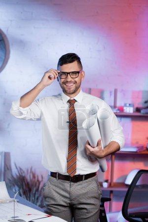 Photo pour Architecte ajuster les lunettes tout en se tenant debout avec des plans roulés et souriant à la caméra - image libre de droit