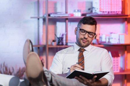 Photo pour Architecte souriant assis avec les jambes sur le bureau et l'écriture dans le carnet - image libre de droit