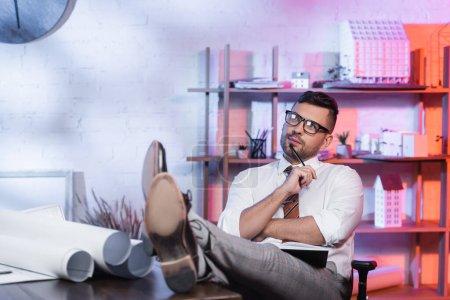Photo pour Architecte réfléchi regardant loin tout en étant assis avec les jambes sur le bureau - image libre de droit